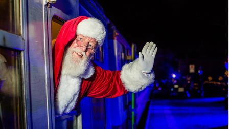Santa Claus waving from the open window of a steam train.