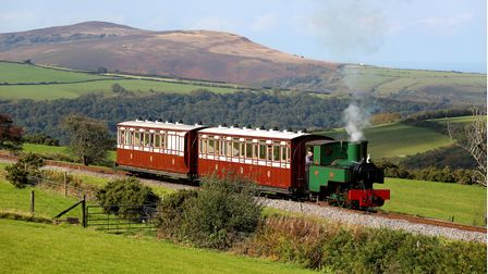 A steam train on the Lynton & Barnstaple Railway with the rolling hills of Exmoor in the background.