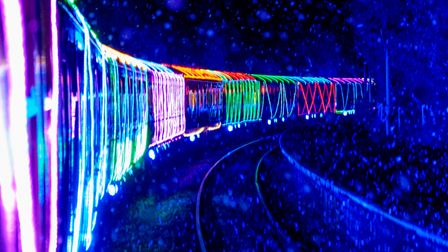 A steam train's lit-up carriages festooned with Christmas fairy lights.