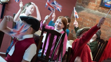 Pupils at Stratford St Mary Primary School waving their Union Jack flags