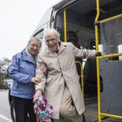 woman with elderly man getting off a minibus