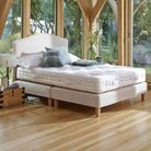 In an airy and light room, a king size mattress sits on a cream frame in front of the window.
