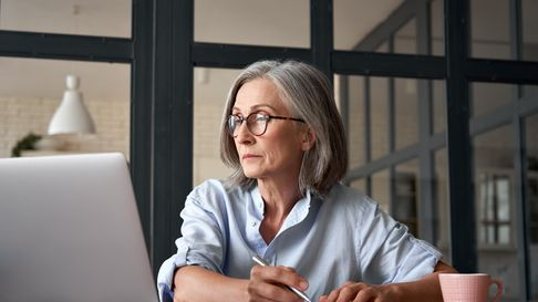 Serious mature older adult woman watching training webinar on laptop working from home or in office.