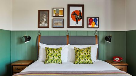 A hotel bed with coloured cushions on top.