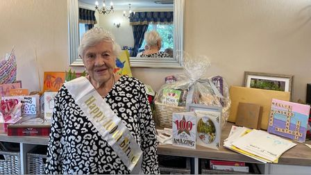 Nellie standing in front of her 130 cards and gifts.