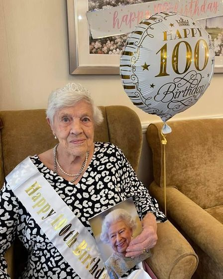 Nellie holding her card from the Queen with a 100th birthday balloon next to her.