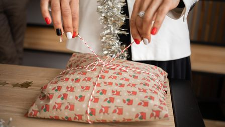 A woman with festively painted nails ties a bow on a Christmas present.