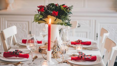 A table has been set for dinner and decorated with festive colours, flowers, and candles.