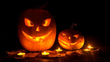 Two pumpkin jack lantern with smiles carved on Halloween with a candle backlight