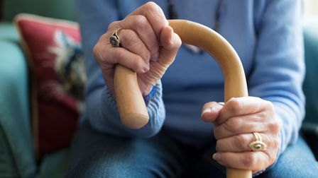 A woman receiving adult social care grips her walking cane