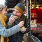 Mature couple are enjoying sharing some paella from a christmas market stall