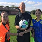 Lisa Quaintance of Plainmoor Ladies and Steph Warren of Activate with ref Maurice Beckenham, holding a football