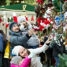 Ordinary happy family with little girls standing at coniferous Christmas souvenirs counter. Focus on