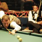 Former world snooker champion Steve Davis, of England takes his next shot as he partners Alex Lely (