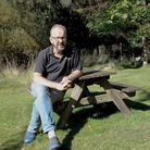 Ruud JansenVenneboer sitting at a bench on a grassy lawn