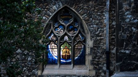 A stained glass window lit up at St Edward's Church in Market Place, Romford
