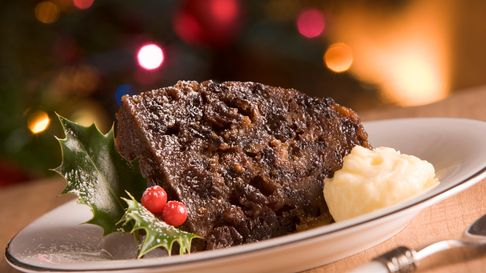 Portion of Christmas Pudding On Plate With Brandy Butter In Front Of Christmas Tree