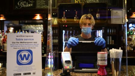 A member of staff in PPE waits to serve drinkers at the reopening of a Wetherspoons pub. Photograph: