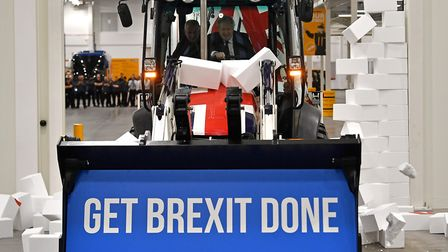 Britain's Prime Minister and Conservative party leader Boris Johnson drives a Union flag-themed JCB