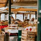 Several market stalls are laden with food, ready for customers