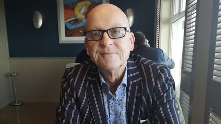 Councillor Markiewicz wearing square glasses, blue patterned shirt and dark blue and red pinstripe blazer.