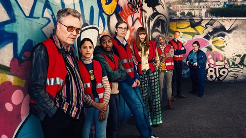 A promotional image of the cast lined up against a graffitied wall, with Walken at the front