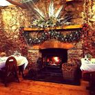 A festively decorated fireplace with two tables on either side that are laid for dinner