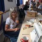 Lady with sewing machine and other 'fixers' at work at Sidmouth Repair Cafe