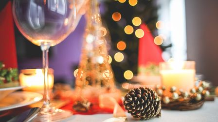 A table adorned with wine glasses, pinecones, and Christmas decorations