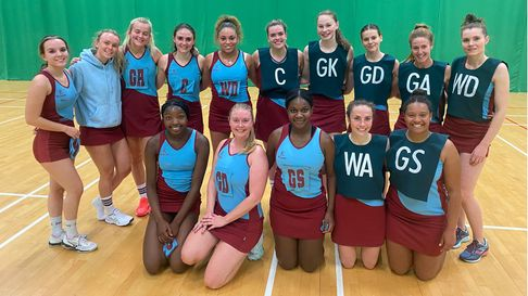 Two teams of netballers in their playing gear