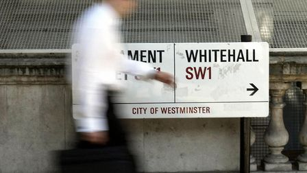 A commuter passes a street sign on Whitehall, central London; Chris Young