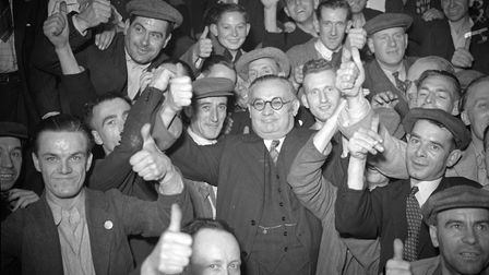 circa 1940: In the centre, wearing glasses and surrounded by cloth capped workers giving a thumbs u