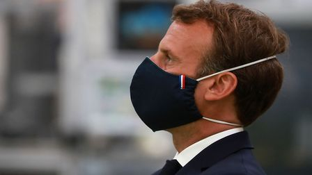 French President Emmanuel Macron, wearing a protective face mask, looks on as he visits a factory of