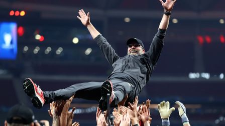 Jurgen Klopp, Manager of Liverpool is thrown in the air as he celebrates with his players and staff