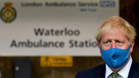 Prime Minister Boris Johnson, wearing a face mask, during a visit to the headquarters of the London