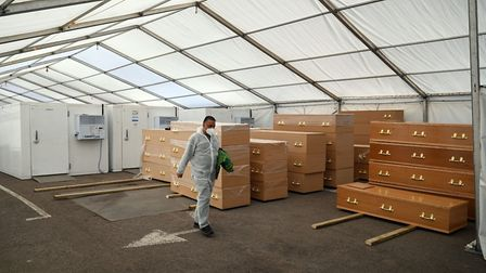 A trained volunteer walks past coffins stacked next to refrigeration units inside the temporary mort