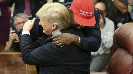 President Donald Trump hugs rapper Kanye West during a meeting in the Oval office