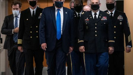 US President Donald Trump wears a mask as he visits Walter Reed National Military Medical Center in