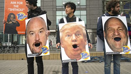People hold up images of Harvey Weinstein, President Trump and Louis CK during the Women's March i