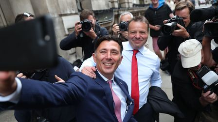 Brexit campaign donor and businessman Arron Banks (CR) and Leave.EU campaigner Andy Wigmore (CL) tak
