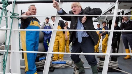 British Prime Minister Boris Johnson speaks to members of the crew on the Carvela at Stromness Harbo