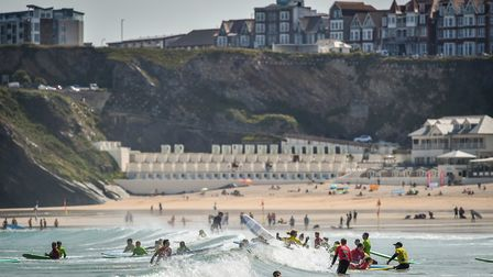 Surfers play in the waves during the hot sunshine on Great Western beach in Newquay, Cornwall. Photo