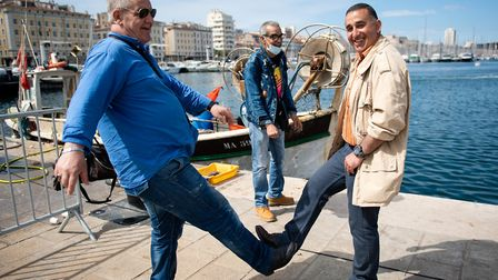 Two men pose as they greet each other with their feet in the Vieux Port of Marseille southern France