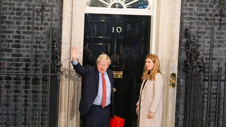 Prime Minister Boris Johnson and his partner Carrie Symonds enter Downing Street. (Photo by Giannis