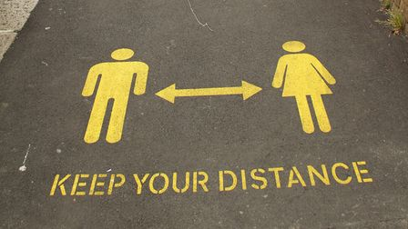 A view of a Social distancing sign stencilled on a footpath during a demonstration. (Photo by David