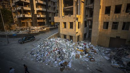 People walk next debris from destroyed buildings near the site of last week's explosion that hit the