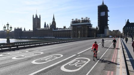 Cyclists riding across an empty Westminster Bridge in London, the day after Prime Minister Boris Joh