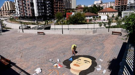 Kosovo artist Alkent Pozhegu works on the final touches of a mosaic made with grains and seeds, depi