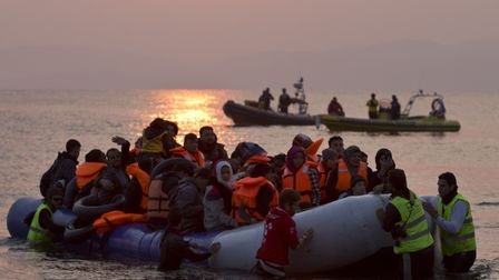 Volunteers help migrants and refugees on a dingy as they arrive on the shore of the northeastern Gre