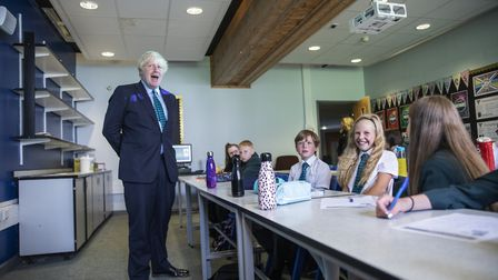 Prime Minister Boris Johnson, wearing the school tie he was presented with on arrival, speaks to a class of year 7 pupils...